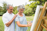 Content retired woman painting on canvas and talking with husband