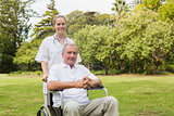 Man sitting in a wheelchair with his nurse pushing him