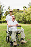 Happy man sitting in a wheelchair with his nurse pushing him