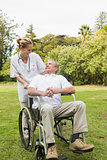 Happy man sitting in a wheelchair talking with his nurse pushing him