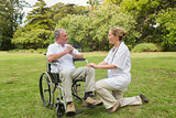 Smiling man in a wheelchair talking with his nurse kneeling beside