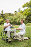 Happy man in a wheelchair talking with his nurse kneeling beside