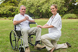 Cheerful man in a wheelchair with his nurse kneeling beside