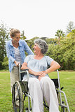 Happy mature woman in wheelchair talking with daughter