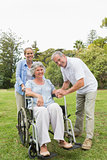 Woman sitting in wheelchair with husband and daughter