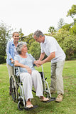 Mature woman in wheelchair with husband and daughter