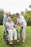 Retired woman in wheelchair with husband and daughter