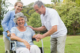 Happy woman in wheelchair with daughter and husband