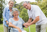 Smiling woman in wheelchair with daughter and husband