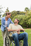 Happy man in wheelchair talking with partner