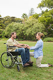 Happy man in wheelchair with partner kneeling beside him
