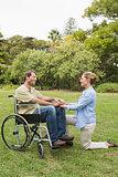 Happy man in wheelchair with partner kneeling beside him