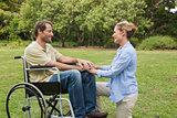 Smiling man in wheelchair with partner kneeling beside him