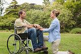 Content man in wheelchair with partner kneeling beside him