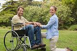 Handsome man in wheelchair with partner kneeling beside him