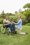 Attractive man in wheelchair with partner kneeling beside him