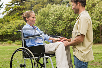 Attractive woman in wheelchair with partner kneeling beside her