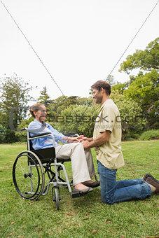 Blonde woman in wheelchair with partner kneeling beside her