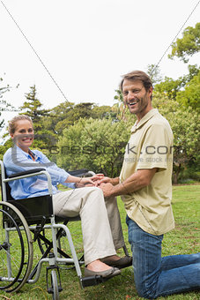 Blonde woman smiling in wheelchair with partner kneeling beside her