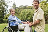 Happy woman in wheelchair with partner kneeling beside her