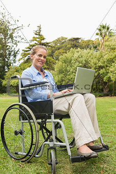 Smiling young woman in a wheelchair with a laptop