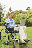 Happy woman in a wheelchair using a laptop