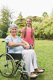 Smiling granddaughter with grandmother in her wheelchair