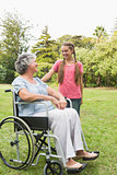 Happy granddaughter talking with grandmother in her wheelchair