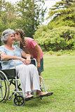 Granddaughter kissing cheek of grandmother in wheelchair