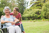 Granddaughter embracing grandmother in wheelchair