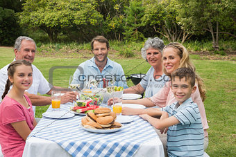Multi generation family having dinner outside at picnic table