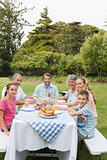 Multi generation family at picnic table having dinner outside