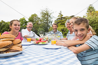 Extended family having dinner outdoors at picnic table