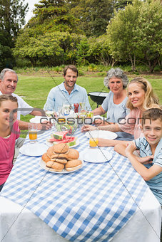 Cheerful extended family having dinner outdoors at picnic table