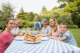 Smiling extended family waiting for barbecue being cooked by father