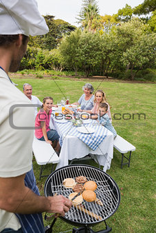 Happy extended family having a barbecue being cooked by father in chefs hat