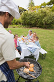 Smiling extended family having a barbecue being cooked by father in chefs hat