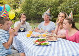 Family celebrating little girls birthday outside at picnic table