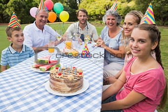 Extended family celebrating little girls birthday outside at picnic table