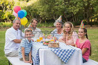 Family smiling at camera at birthday party