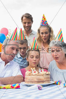 Cheeful family watching girl blowing out candles at birthday party