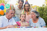 Cheerful extended family watching girl blowing out birthday candles