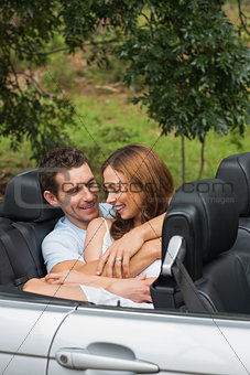 Cute couple cuddling in the backseat and chatting