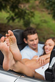 Happy couple cuddling in the backseat with focus on foot