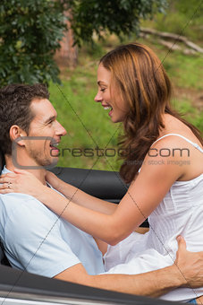 Young couple feeling romantic in back seat and laughing