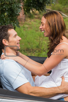Happy couple feeling romantic in back seat and laughing