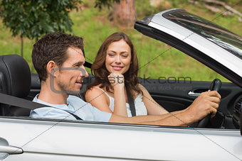 Young couple driving in a silver convertible