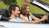 Laughing couple driving in a silver convertible