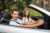 Happy couple driving in a silver convertible