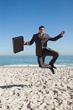 Cheerful businessman jumping on the beach